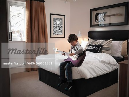 Boy playing guitar in bedroom Stock Photos Masterfile. Guitar Bedroom