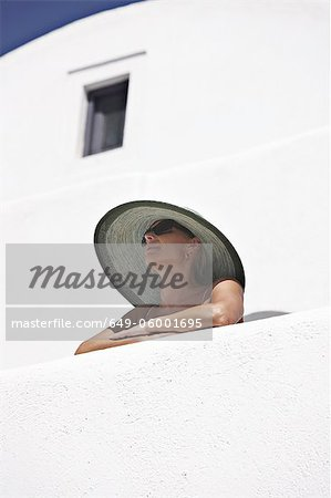 Woman in sunhat standing on balcony