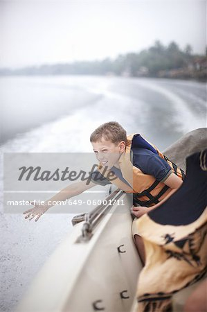 Teenage boy reaching to water from boat Stock Photo - Premium Royalty-Free, Image code: 649-06001711