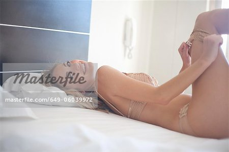 Woman pulling on pantyhose on bed Stock Photo - Premium Royalty-Free, Image code: 649-06039972