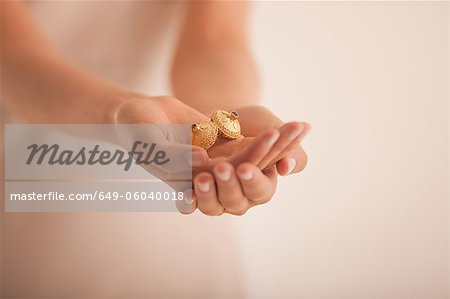 Woman holding golden ornaments Stock Photo - Premium Royalty-Free, Image code: 649-06040018