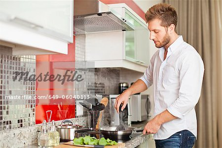Man cooking in kitchen Stock Photo - Premium Royalty-Free, Image code: 649-06040113