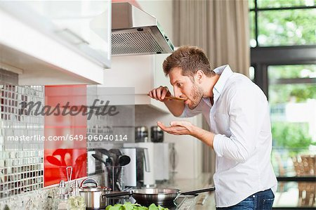 Man tasting food in kitchen Stock Photo - Premium Royalty-Free, Image code: 649-06040114