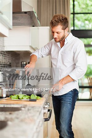 Smiling man cooking in kitchen Stock Photo - Premium Royalty-Free, Image code: 649-06040115