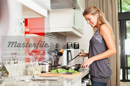 Smiling woman cooking in kitchen Stock Photo - Premium Royalty-Free, Image code: 649-06040116