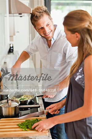 Couple cooking together in kitchen Stock Photo - Premium Royalty-Free, Image code: 649-06040118
