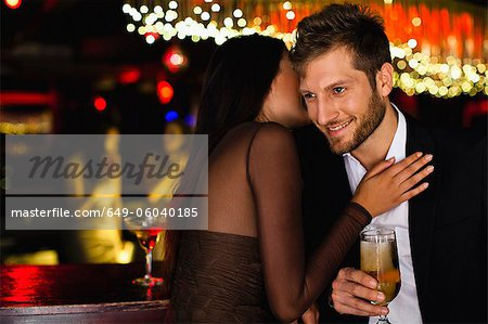 Smiling couple whispering at bar Stock Photo - Premium Royalty-Free, Image code: 649-06040185