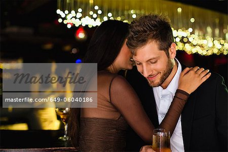 Smiling couple whispering at bar Stock Photo - Premium Royalty-Free, Image code: 649-06040186