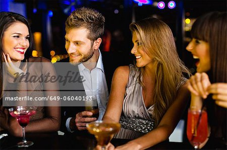 Man talking to women at bar Stock Photo - Premium Royalty-Free, Image code: 649-06040193