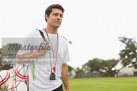 Coach carrying soccer balls on pitch Stock Photo - Premium Royalty-Free, Image code: 649-06040285