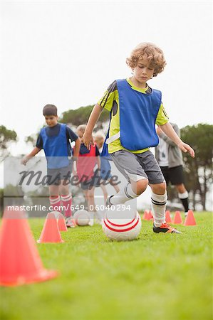 Childrens soccer team training on pitch Stock Photo - Premium Royalty-Free, Image code: 649-06040294