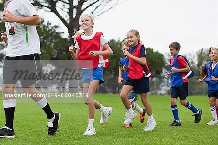 Coach training children on field Stock Photo - Premium Royalty-Free, Image code: 649-06040319