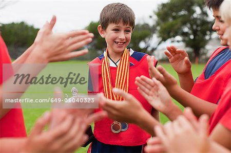 Children cheering teammate with trophy Stock Photo - Premium Royalty-Free, Image code: 649-06040323