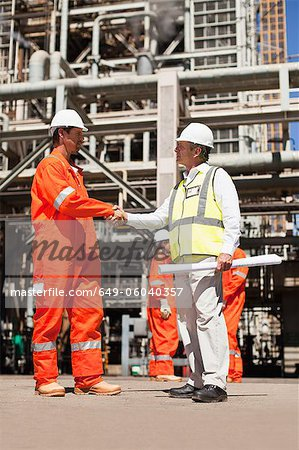 Workers shaking hands at oil refinery Stock Photo - Premium Royalty-Free, Image code: 649-06040357