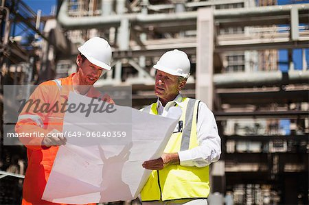 Workers with blueprints at oil refinery Stock Photo - Premium Royalty-Free, Image code: 649-06040359