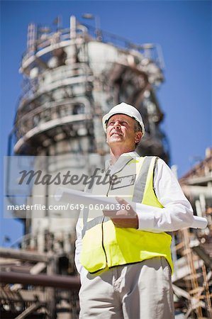 Worker with blueprints at oil refinery Stock Photo - Premium Royalty-Free, Image code: 649-06040366