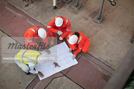 Workers with blueprints at oil refinery Stock Photo - Premium Royalty-Free, Image code: 649-06040372