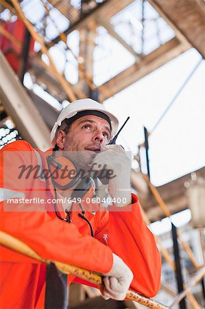 Worker with walkie talkie on site Stock Photo - Premium Royalty-Free, Image code: 649-06040400