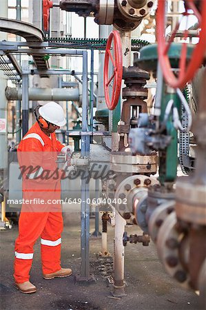 Worker adjusting gauge at oil refinery Stock Photo - Premium Royalty-Free, Image code: 649-06040402
