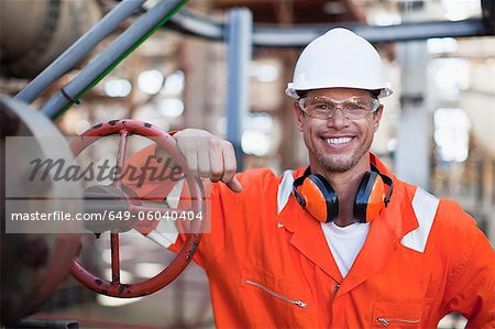 Worker smiling at oil refinery Stock Photo - Premium Royalty-Free, Image code: 649-06040404
