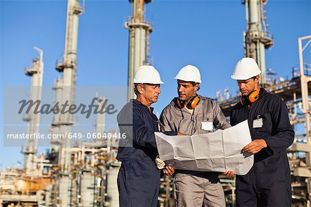 Workers with blueprints at oil refinery Stock Photo - Premium Royalty-Free, Image code: 649-06040416