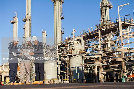 Workers with blueprints at oil refinery Stock Photo - Premium Royalty-Free, Image code: 649-06040417