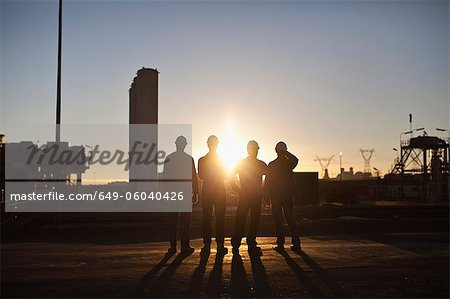 Silhouette of workers at oil refinery Stock Photo - Premium Royalty-Free, Image code: 649-06040426