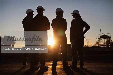 Silhouette of workers at oil refinery Stock Photo - Premium Royalty-Free, Image code: 649-06040427