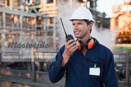 Worker using walkie talkie on site Stock Photo - Premium Royalty-Free, Image code: 649-06040430