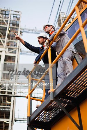 Workers talking at oil refinery Stock Photo - Premium Royalty-Free, Image code: 649-06040435