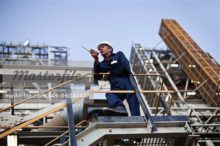 Worker using walkie talkie on site Stock Photo - Premium Royalty-Free, Image code: 649-06040437