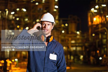 Worker on cell phone at oil refinery Stock Photo - Premium Royalty-Free, Image code: 649-06040447