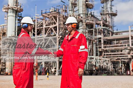 Workers shaking hands at oil refinery Stock Photo - Premium Royalty-Free, Image code: 649-06040450