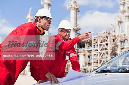Workers with blueprints at oil refinery Stock Photo - Premium Royalty-Free, Image code: 649-06040455