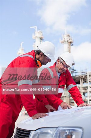 Workers with blueprints at oil refinery Stock Photo - Premium Royalty-Free, Image code: 649-06040456