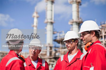 Workers talking at oil refinery Stock Photo - Premium Royalty-Free, Image code: 649-06040458