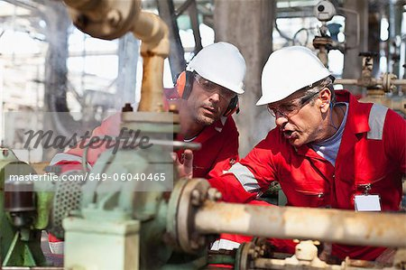 Workers examining equipment on site Stock Photo - Premium Royalty-Free, Image code: 649-06040465