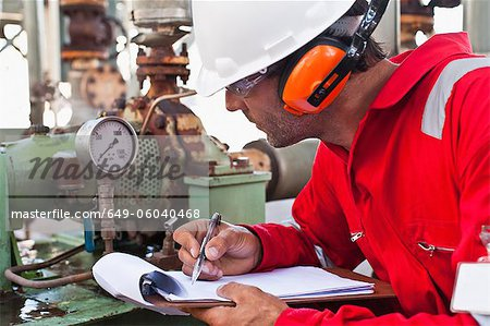 Worker noting gauge at oil refinery Stock Photo - Premium Royalty-Free, Image code: 649-06040468