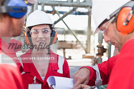 Workers talking at oil refinery Stock Photo - Premium Royalty-Free, Image code: 649-06040473