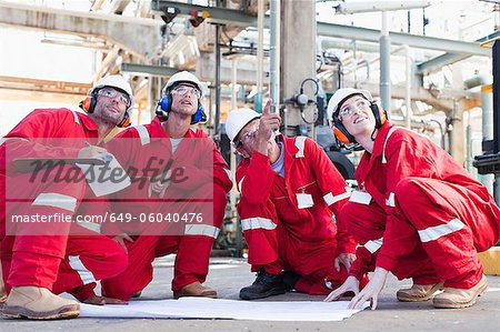 Workers with blueprints at oil refinery Stock Photo - Premium Royalty-Free, Image code: 649-06040476