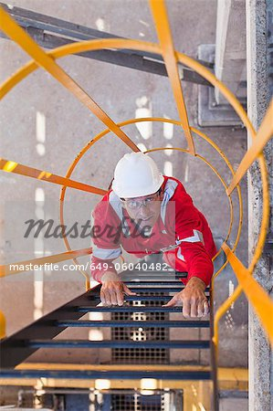 Worker climbing ladder at oil refinery Stock Photo - Premium Royalty-Free, Image code: 649-06040482