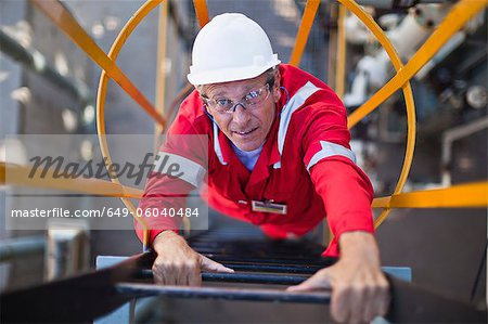 Worker climbing ladder at oil refinery Stock Photo - Premium Royalty-Free, Image code: 649-06040484