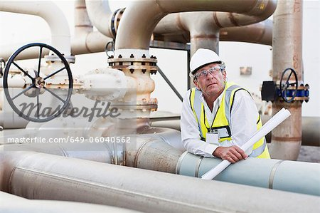 Worker on pipes at chemical plant Stock Photo - Premium Royalty-Free, Image code: 649-06040562
