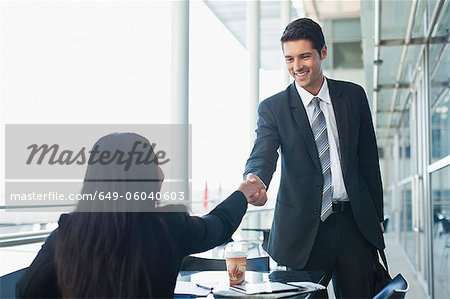 Business people shaking hands in cafe Stock Photo - Premium Royalty-Free, Image code: 649-06040603