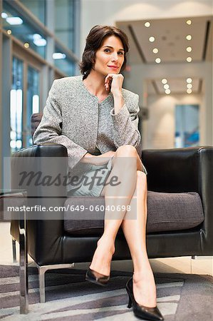 Businesswoman sitting in armchair Stock Photo - Premium Royalty-Free, Image code: 649-06040698