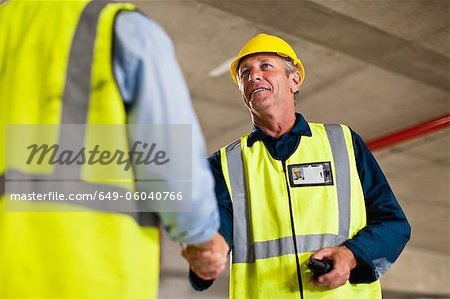 Workers shaking hands on site Stock Photo - Premium Royalty-Free, Image code: 649-06040766