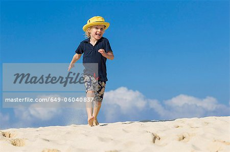 Boy walking on sandy beach Stock Photo - Premium Royalty-Free, Image code: 649-06040837