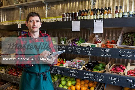 Grocer using tablet computer in store Stock Photo - Premium Royalty-Free, Image code: 649-06041012