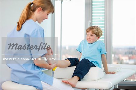 Doctor examining boys feet in office Stock Photo - Premium Royalty-Free, Image code: 649-06041075
