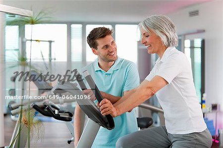 Trainer working with woman in gym Stock Photo - Premium Royalty-Free, Image code: 649-06041096